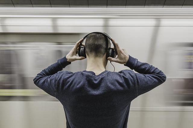 Nann mit Kopfhörern und vorbei fahrender Zug.